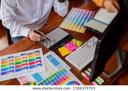 Graphic design and color swatches and pens on a desk. Architectural drawing with work tools and accessories. #1186379701