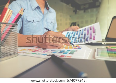 Graphic design and color swatches and pens on a desk. Architectural drawing with work tools and accessories. #574099243