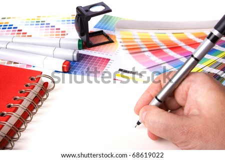 graphic design and coloured swatches and pens on a desk