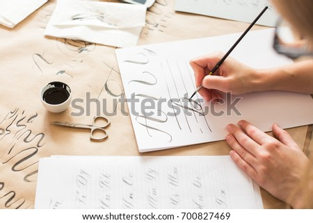 graphic design, handwriting, creation concept. tender little hands of female painter inscribing ornamental decorated letters on the white lined paper with help of thin tip of the brush and black ink #700827469