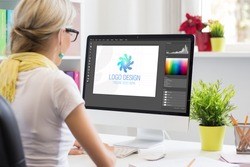 Graphic designer creating company's logo on desktop computer