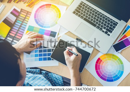 Graphic designer drawing on graphics tablet at workplace #744700672