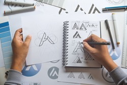 Graphic designer drawing sketch design creative Ideas draft Logo product trademark label brand artwork. Graphic designer studio Concept.