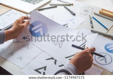 Graphic designer drawing sketch design creative Ideas draft Logo product trademark label brand artwork. Graphic designer studio Concept. #1174987573