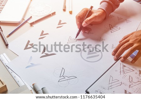 Graphic designer drawing sketch design creative Ideas draft Logo product trademark label brand artwork. Graphic designer studio Concept. #1176635404