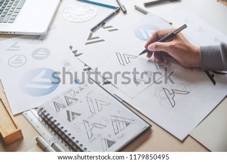 Graphic designer drawing sketch design creative Ideas draft Logo product trademark label brand artwork. Graphic designer studio Concept. #1179850495