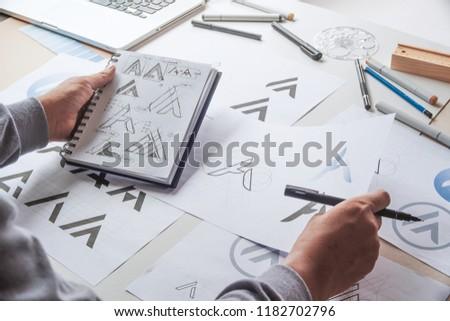 Graphic designer drawing sketch design creative Ideas draft Logo product trademark label brand artwork. Graphic designer studio Concept. #1182702796