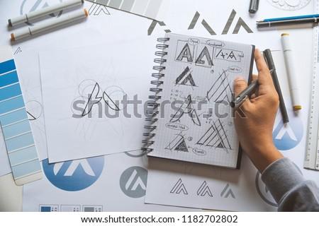 Graphic designer drawing sketch design creative Ideas draft Logo product trademark label brand artwork. Graphic designer studio Concept. #1182702802