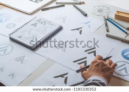 Graphic designer drawing sketch design creative Ideas draft Logo product trademark label brand artwork. Graphic designer studio Concept. #1185330352