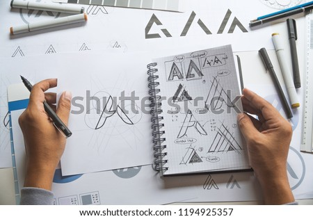 Graphic designer drawing sketch design creative Ideas draft Logo product trademark label brand artwork. Graphic designer studio Concept. #1194925357