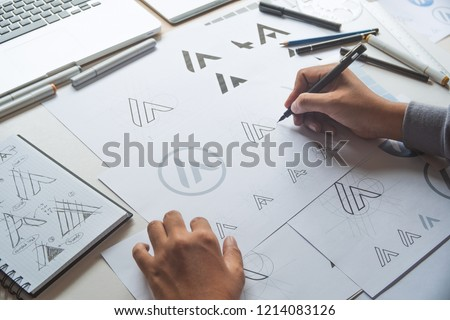 Graphic designer drawing sketch design creative Ideas draft Logo product trademark label brand artwork. Graphic designer studio Concept. #1214083126