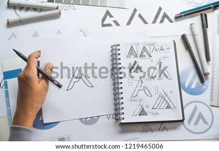 Graphic designer drawing sketch design creative Ideas draft Logo product trademark label brand artwork. Graphic designer studio Concept. #1219465006