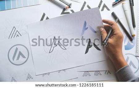 Graphic designer drawing sketch design creative Ideas draft Logo product trademark label brand artwork. Graphic designer studio Concept. #1226185111