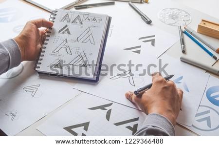 Graphic designer drawing sketch design creative Ideas draft Logo product trademark label brand artwork. Graphic designer studio Concept. #1229366488