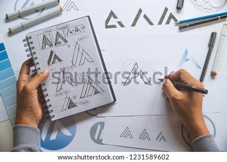 Graphic designer drawing sketch design creative Ideas draft Logo product trademark label brand artwork. Graphic designer studio Concept. #1231589602