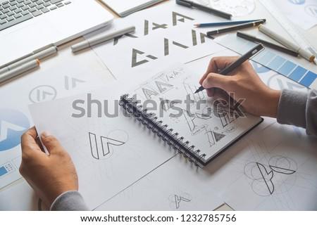 Graphic designer drawing sketch design creative Ideas draft Logo product trademark label brand artwork. Graphic designer studio Concept. #1232785756