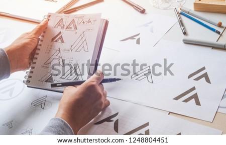 Graphic designer drawing sketch design creative Ideas draft Logo product trademark label brand artwork. Graphic designer studio Concept. #1248804451