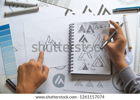 Graphic designer drawing sketch design creative Ideas draft Logo product trademark label brand artwork. Graphic designer studio Concept. #1261157074