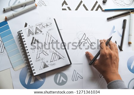 Graphic designer drawing sketch design creative Ideas draft Logo product trademark label brand artwork. Graphic designer studio Concept. #1271361034