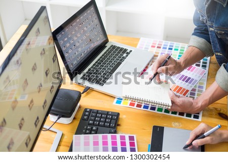 graphic designer team working on web design using color swatches editing artwork using tablet and a stylus At Desks In Busy Creative Office #1300302454