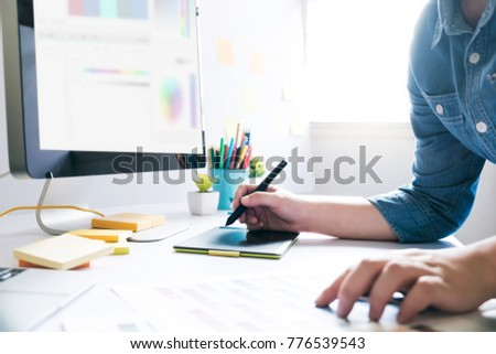 Graphic designer using graphics tablet to do work at desk #776539543