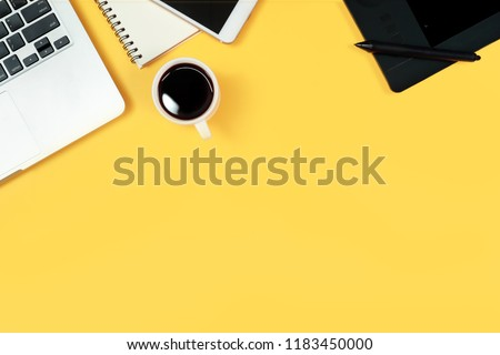 graphic designer working desk top view with laptop computer, pen display, tablet stylus, office supplies and coffee cup on yellow pastel background #1183450000
