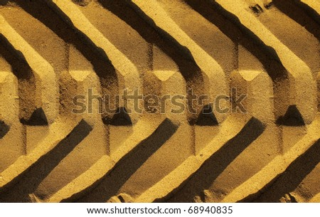 Graphic photo of a wide tire track in golden sand