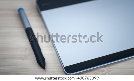 Graphic tablet and pen on wooden desk #490765399