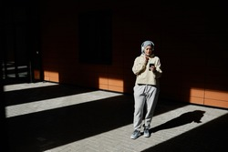 Graphic wide angle portrait of modern Middle-Eastern woman using smartphone in city lit by sunlight and wearing headphones, copy space