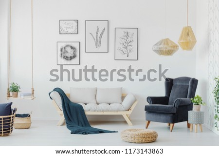 Graphics above a wooden couch with pillows, armchair and swing with a plant in a creative living room interior. Real photo #1173143863