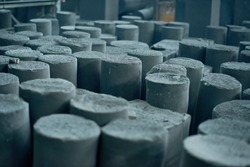 Graphite manufactured articles with unequal height standing at production department of modern plant, close-up shot