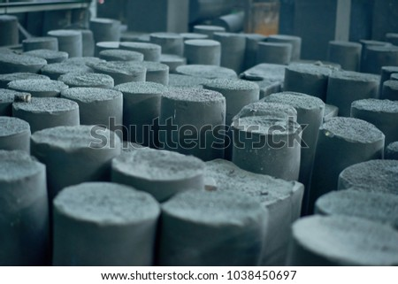 Graphite manufactured articles with unequal height standing at production department of modern plant, close-up shot #1038450697