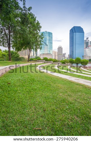 Grass field in Bangkok city Benchakitti Park with modern office building background