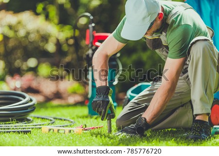 Grass Field Sprinklers Installation by Professional Caucasian Garden Systems Installator. - Shutterstock ID 785776720