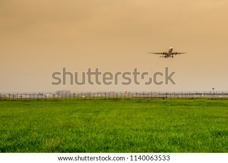 Grass meadow with airplane at sunset #1140063533