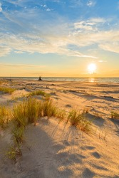 Grass on sand dune and sunset over Leba beach, Baltic Sea, Poland