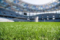 Grass on stadium in sunlight. Closeup of a green football field. Wet stadium grass in the morning light during watering irrigation. Close up macro of soccer or football field. green grass field