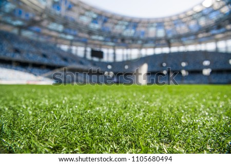Grass on stadium in sunlight. Closeup of a green football field. Wet stadium grass in the morning light during watering irrigation. Close up macro of soccer or football field. green grass field - Shutterstock ID 1105680494
