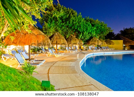 Grass umbrella with lounges at a swimming pool at a caribbean resort at night, dawn time