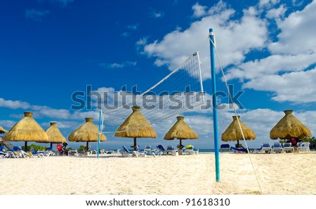 Grass umbrellas at a beach with volleyball net in the middle