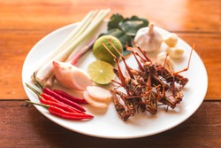 Grasshopper fried insect plates with vegetables on an old wooden background. Insect food is the healthy meal high protein diet concept.