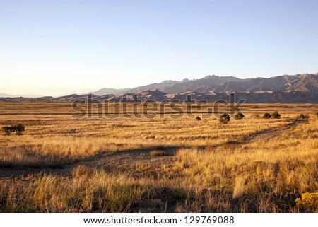 Grasslands at sunset with the Great Colorado Sand Dunes in the distance