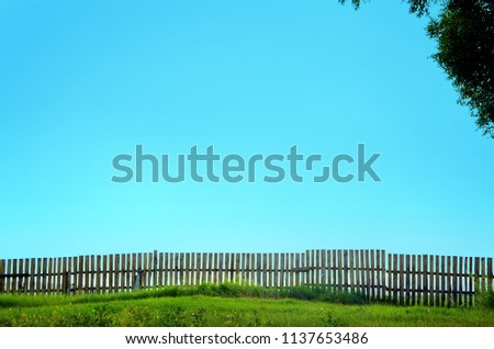 grassy farmer field fence with low wooden fence with blue sky
