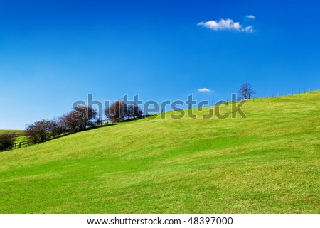 Grassy green hill with a beautiful clear blue sky