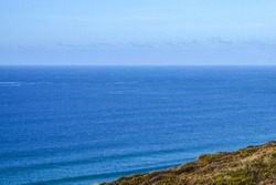 Grassy headlands hide the blue waters of the Atlantic bring peeling waves for surfers. Taken on the rugged North Coast of Cornwall, a popular destination for tourists