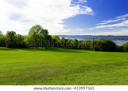 Grassy meadow with trees, sky and clouds - Shutterstock ID 413997565