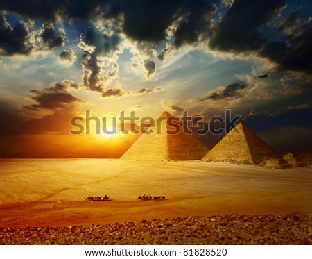 Stock Photo Grate pyramids in Giza valley in Egypt with group of bedouins on camels riding through desert