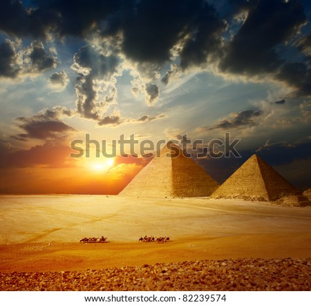 Grate pyramids in Giza valley in Egypt with group of bedouins on camels riding through desert