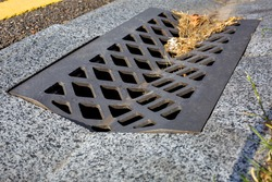 grate with holes for drainage of storm water from a concrete ditch on the side of an asphalt road close-up of a dirty drain canal.