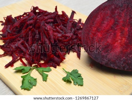 Grated beets and half a beet on a light wooden background